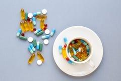 Muchas píldoras coloridas en taza en fondo gris Foto de archivo libre de regalías