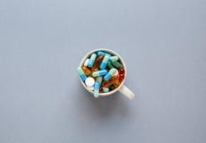 Muchas píldoras coloridas en taza en fondo gris Fotos de archivo libres de regalías
