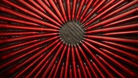 Muchas plumas rojas se mueven en un c?rculo en un fondo de madera negro Oficina o escuela, d?a del concepto del conocimiento, pri almacen de metraje de vídeo
