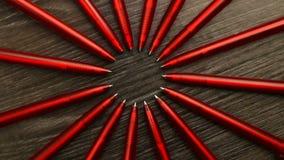 Muchas plumas rojas se mueven en un c?rculo en un fondo de madera negro Oficina o escuela, d?a del concepto del conocimiento, pri almacen de video