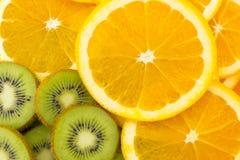 Muchas rebanadas de fruta de kiwi y fruta anaranjada, kiwis frescos y Orán Fotos de archivo libres de regalías