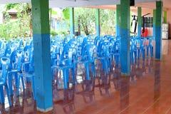 Muchas sillas plásticas azules se arreglan en el piso para las reuniones fotos de archivo