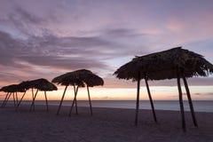 Muchas sombrillas Puesta del sol en frente de mar Imagen de archivo libre de regalías