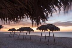 Muchas sombrillas Puesta del sol en frente de mar Fotografía de archivo