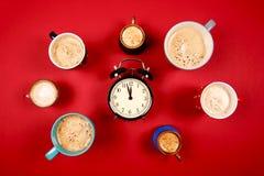 Muchas tazas de café con el despertador Foto de archivo