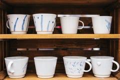 Muchas tazas de cerámica ordinarias en estantes de madera Accesorios de la cocina para cocinar fotografía de archivo