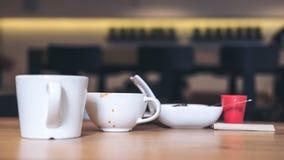 Muchas tazas del café con leche y placa de postre en la tabla de madera Imagenes de archivo
