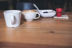 Muchas tazas del café con leche y placa de postre en la tabla de madera Imagen de archivo libre de regalías