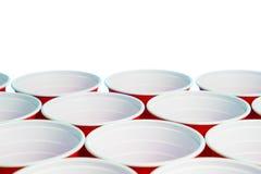 Muchas tazas rojas del partido aisladas en blanco Ciérrese para arriba de los envases del alcohol de la universidad con el espaci Foto de archivo