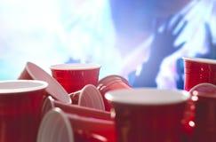 Muchas tazas rojas del partido con la gente de celebración borrosa en el fondo Envases del alcohol de la universidad en posicione foto de archivo libre de regalías