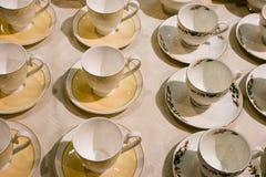 Muchas tazas y platillos de té están en la tabla Fotografía de archivo