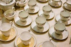 Muchas tazas y platillos de té están en la tabla Fotos de archivo libres de regalías