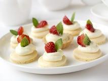 Muchas tortas o mini tarta con las frutas frescas, la crema azotada y las mentas Imagen de archivo