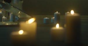 Muchas velas del burning en el piso Velas que queman en los candeleros oscuros, de cristal, llama amarilla de una vela, el sta de