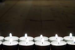 Muchas velas en fila en la tabla de madera vieja Fotos de archivo