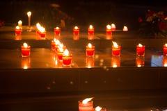 Muchas velas votivas rojas encienden la oscuridad en iglesia Imagen de archivo