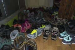 Muchas zapatillas de deporte y zapatos de la montaña en el pasillo del St de Kozya foto de archivo