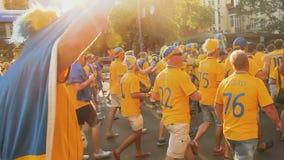 Muchedumbre alegre de fanáticos del fútbol suecos que caminan a través de cantos del canto de la ciudad almacen de video