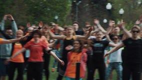 Muchedumbre atlética en el parque de la ciudad que hace los enchufes de salto con las manos rised, calentando almacen de metraje de vídeo
