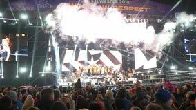 Muchedumbre de danzas de la gente y tirar concierto con los proyectores y efectos especiales del humo sobre un teléfono móvil por almacen de metraje de vídeo