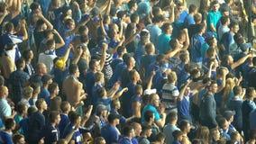 Muchedumbre de fanáticos del fútbol masculinos que cantan y que saltan, animando para el equipo nacional almacen de metraje de vídeo