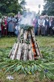 Muchedumbre de gente alrededor de la hoguera que celebra solsticio de verano del pleno verano Imagen de archivo libre de regalías