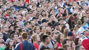 Muchedumbre de gente con el hombre en traje de capitán Jack Sparrow que mira la difusión del partido de fútbol en un cuadrado almacen de video