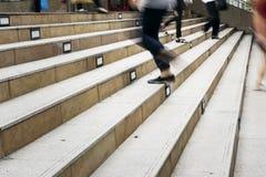 Muchedumbre de gente en el movimiento borroso que camina arriba y abajo de la escalera Fotos de archivo libres de regalías