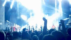 Muchedumbre de gente en un concierto que salta y que baila con las manos para arriba almacen de video