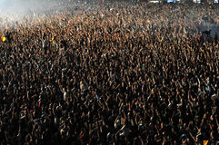 Muchedumbre de gente que aumenta sus manos en un concierto Imágenes de archivo libres de regalías