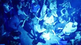 Muchedumbre de gente que baila en una cámara lenta del club almacen de metraje de vídeo