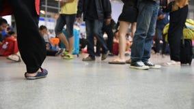 Muchedumbre de gente que camina con equipaje y de mucha gente que se sienta en la estación de autobúses, escena de-enfocada metrajes