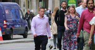 Muchedumbre de gente que camina en la acera de la calle de la ciudad metrajes