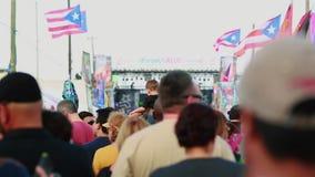 Muchedumbre de gente que da une vuelta durante un festival Banderas puertorriqueñas en el tiro almacen de video