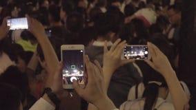 Muchedumbre de gente que filma escena con los teléfonos celulares aumentados almacen de video