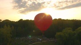 Muchedumbre de gente que mira el balón de aire candente el subir en el cielo iluminado por el sol, festival metrajes