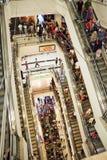 Muchedumbre de las compras en la escalera móvil Fotos de archivo libres de regalías