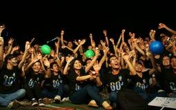 Muchedumbre de mano del aumento de la persona joven sobre hora de la tierra Fotos de archivo libres de regalías