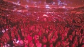 Muchedumbre de miembros religiosos fanáticos que aplauden al predicador, iluminación roja de la secta almacen de video
