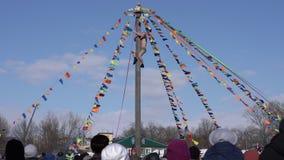 Muchedumbre de subir masculino de observación de la gente al polo de madera para los premios y los regalos