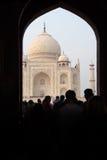 Muchedumbre de turistas que pasan al templo de Taj Mahal a través de un arco, filmado en la ciudad de Agra, la India en noviembre foto de archivo