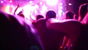 Muchedumbre del concierto en el festival de m?sica en directo Manos del partido para arriba y gente de baile en muchedumbre masiv almacen de video