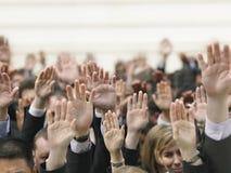 Muchedumbre del negocio que aumenta las manos Foto de archivo libre de regalías