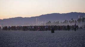 Muchedumbre en la playa durante puesta del sol almacen de video