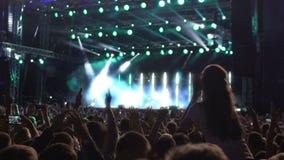 Muchedumbre entusiasta que aplaude sus manos que llaman al grupo musical querido para la repetición almacen de metraje de vídeo