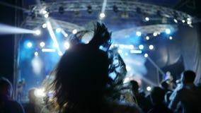 Muchedumbre extática que salta para arriba con los brazos por encima que disfrutan de música en directo antes de etapa brillantem metrajes