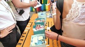 Muchedumbre gay feliz de LGBT en los condones libres y las piruletas del orgullo anual metrajes