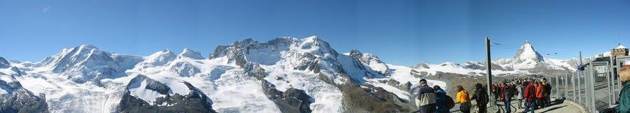 Muchedumbre grande en un café del top de la montaña que disfruta de la vista del CERVINO Fotos de archivo