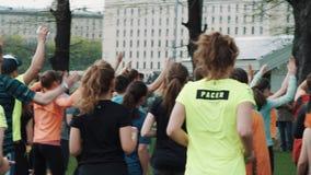 Muchedumbre juguetona en el parque de la ciudad que hace los enchufes de salto con las manos rised, calentando metrajes