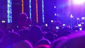 Muchedumbre que hace el partido en un concierto de rock Cámaras del control de las manos con los indicadores digitales almacen de metraje de vídeo